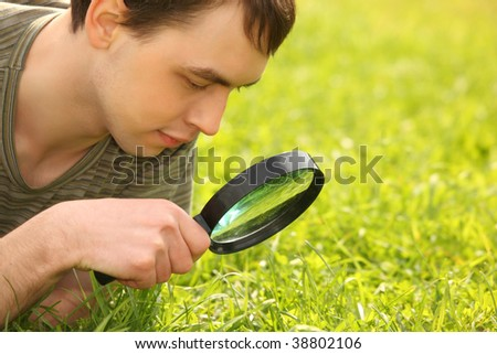 young man looks through magnifier on grass field