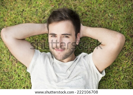 Young man lying and relaxing in grass - stock photo