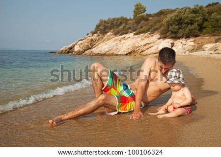 Young man lying at the beach and playing with 9 months old baby - stock photo