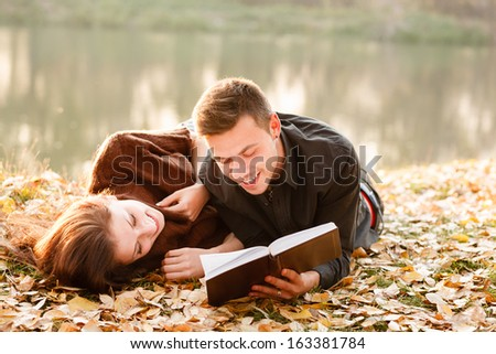 young man lying down near lake reading to his girlfriend book - stock photo