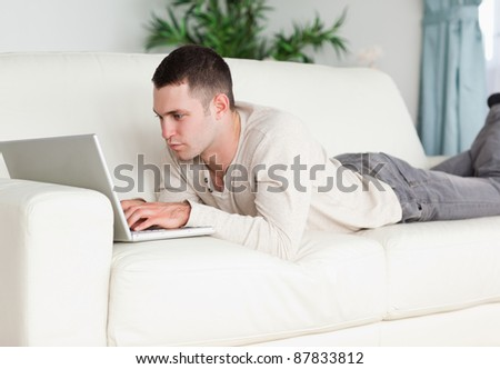 Young man lying on a sofa using a laptop in his living room