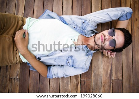 Young man lying on a wooden floor - stock photo