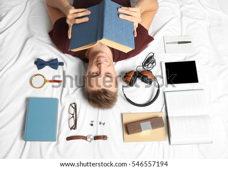Young man lying on bed with different items