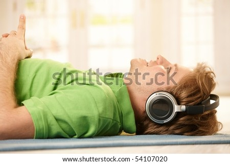 Young man lying on floor wearing headphones, pointing up, smiling.