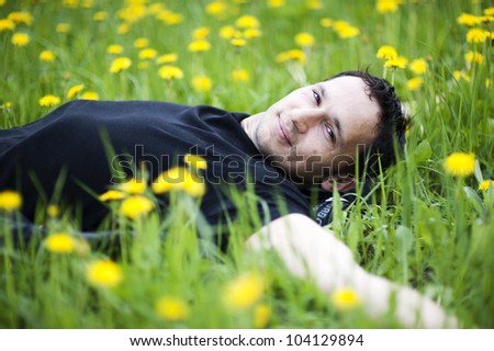 Young man lying on grass with yellow  flowers