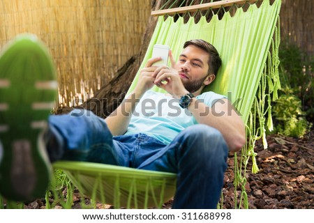 Young man lying on hammok and using smartphone outdoors  - stock photo