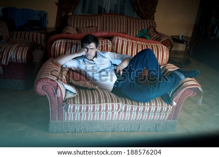 Young man lying on sofa and watching TV at night - stock photo
