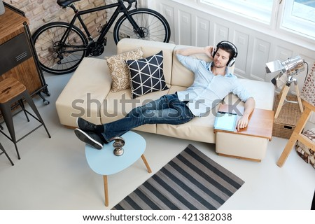 Young man lying on sofa at home, listening to music through headphones eyes closed. - stock photo