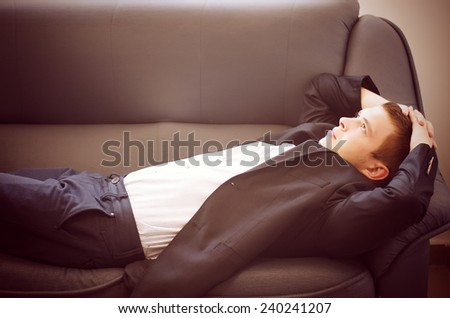 Young Man Lying on Sofa Relaxing with Hands Behind Head Looking Off Into Space as if Daydreaming