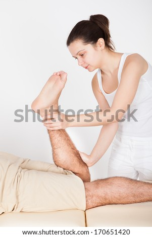 Young Man Lying On Table Getting Foot Massage From Masseuse - stock photo