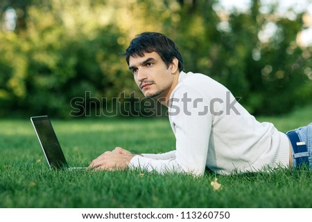 Young man lying on the grass and using laptop outdoor, looking to the side - stock photo