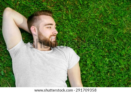 Young man lying on the grass in park.