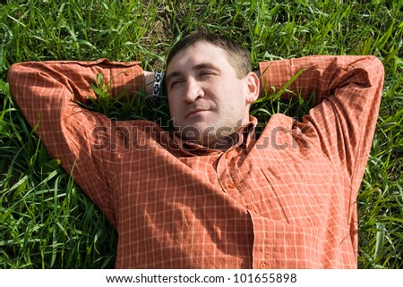 young man lying on the grass with his hands behind his head