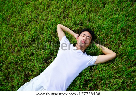 young man lying on the green grass - stock photo
