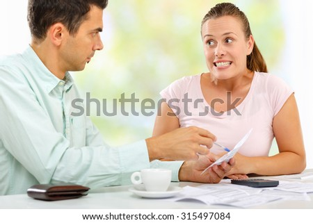 Young man mad at his wife for making large bills. She tries to soften him - stock photo