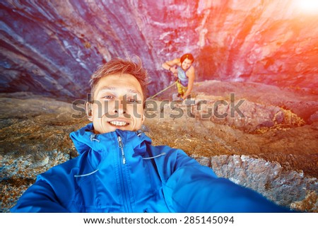 young  man make selfie on the rock background - stock photo