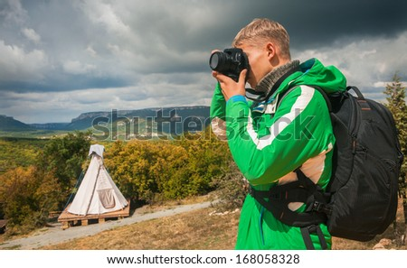Young man makes outdoor shots in high mountain camp - stock photo