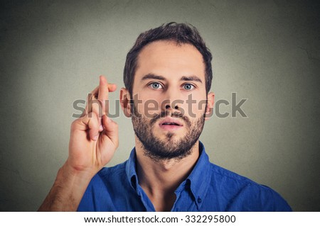 Young man making a wish crossing his fingers isolated on gray wall background - stock photo
