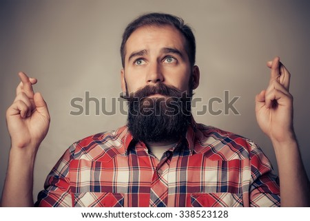 Young man making a wish crossing his fingers  on gray wall background - stock photo