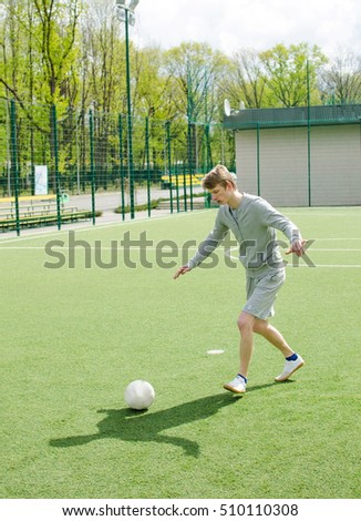Young man making football freestyle on the field