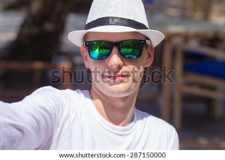 Young man making his selfie on beach at outdorr cafe - stock photo
