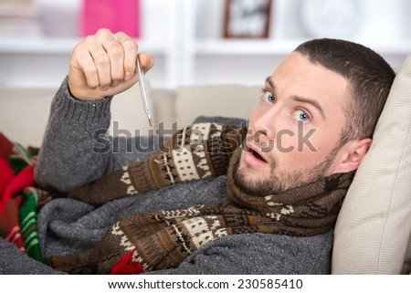 Young man measures the temperature is lying on the bed. - stock photo