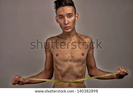 Young man measuring himself. Skinny young man posing fashion with a centimeter, anorexic look - stock photo