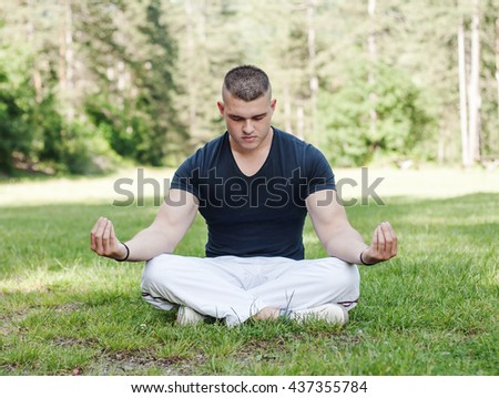 young man meditating in silence on the green meadow