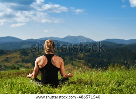 young man meditating in yoga in mountain