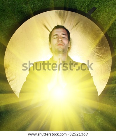 Young man meditating with rays of light coming out of his body. - stock photo