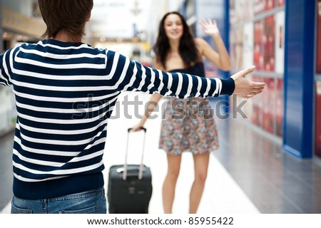 Young man meeting his girlfriend with opened arms at airport arrival hall