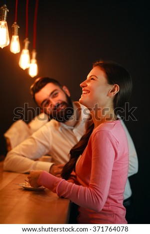 Young man met behind the bar with girl in a nightclub - stock photo