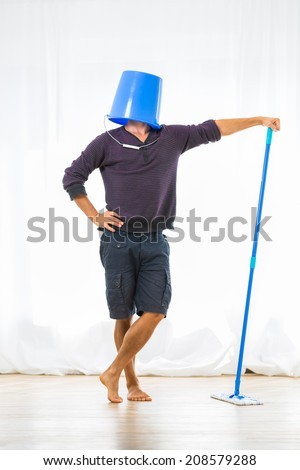Young man mopping the floor. Or is he? - stock photo