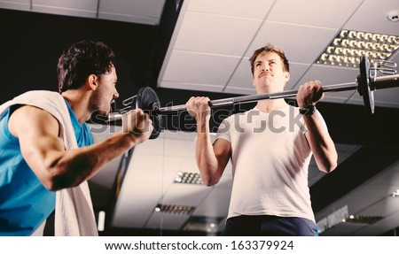 Young man motivating gym buddy during bicep exercise - stock photo