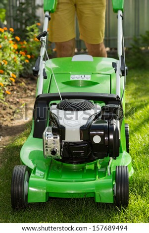 Young man mowing the lawn. - stock photo