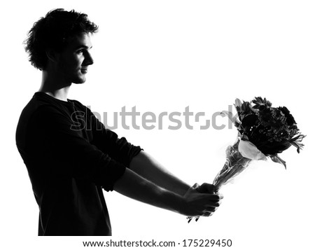 young man offering flowers bouquet silhouette in studio isolated on white background