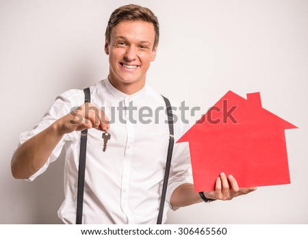 Young man on a gray background holding a paper house - stock photo