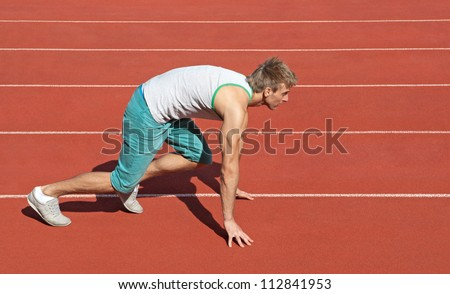 Young man on a racetrack preparing to run.