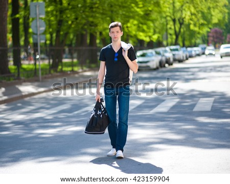 Young man on a street in the city in casual clothes - stock photo