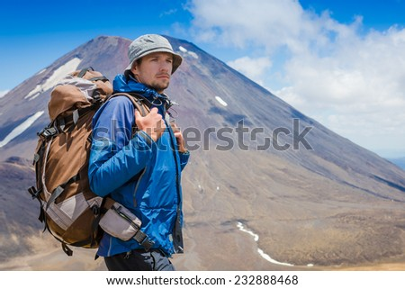 Young man on a sunny day hiking in high mountains. Tongariro. New Zealand