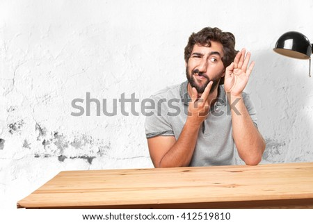 young man on a table. worried expression - stock photo