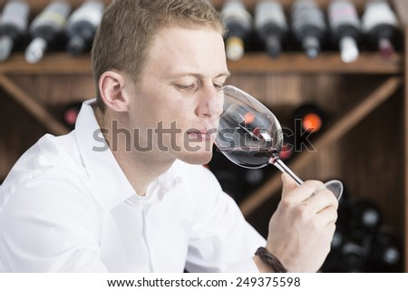 young man on a wine tasting session on the olfactory phase is analyzing the red wine with the wineglass in the nose at a restaurant - focus on the man face
