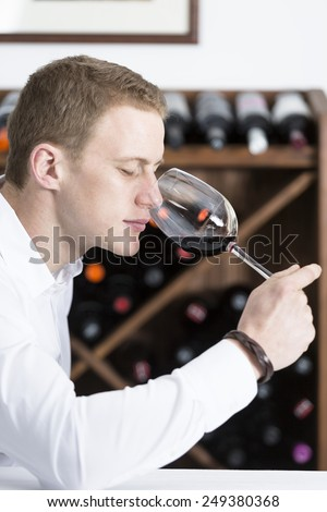 young man on a wine tasting session on the olfactory phase is analyzing the wine with the wine glass in the nose at a restaurant focus on the man face - stock photo