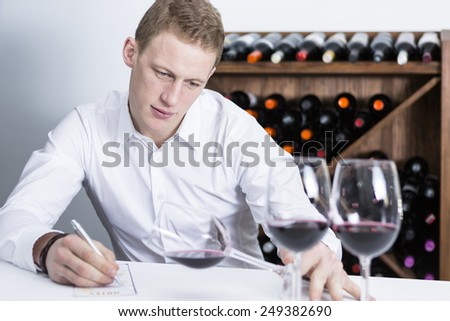 young man on a wine tasting session on the visual phase is writing down in a wine tasting sheet at a restaurant  - focus on the man face