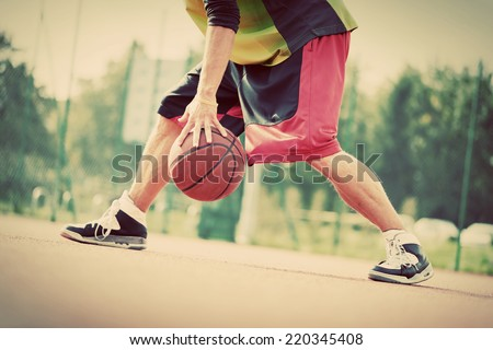 Young man on basketball court dribbling with ball. Streetball, training, activity. Real and authentic, vintage mood. - stock photo