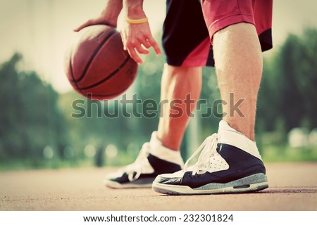 Young man on basketball court dribbling with ball. Streetball, training, activity. Real and authentic, vintage mood.