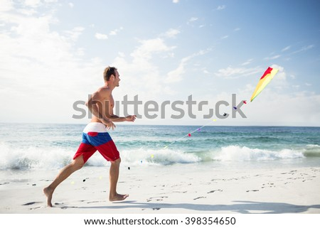 Young man on beach playing with a kite on a sunny day - stock photo