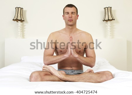 Young man on bed practicing yoga - stock photo