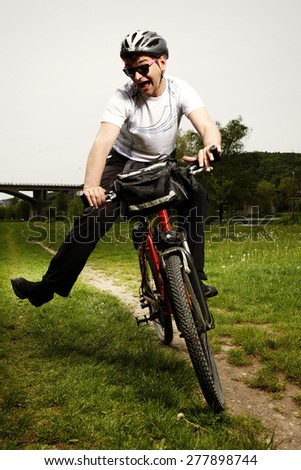 Young man on bicycle falling down - stock photo
