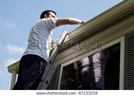 Young man on latter cleaning house gutters